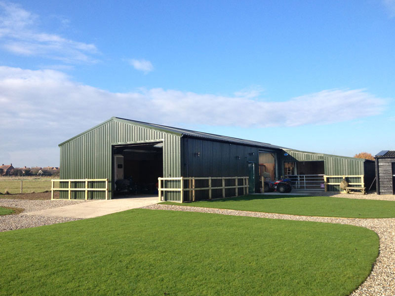 Beautiful sunny day with agricultural barn set around lush green grass