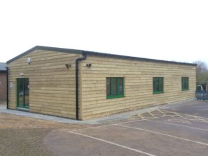 Wood clad school sports hall with forest green coloured windows & doors