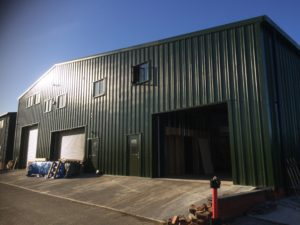 Large Juniper Green Joinery Factory & Offices set before a clear blue sky line